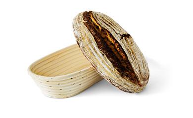 Banneton com pão fermentado naturalmente ao lado